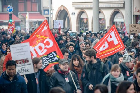 reforms: STRASBOURG, FRANCE - 9 MAR 2016: Crowd marching with Communist flags as thousands of people demonstrate as part of nationwide day of protest against proposed labor reforms by Socialist Government