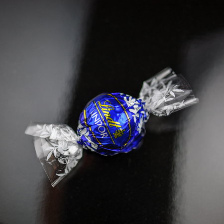 lindt: KILCHBERG, SWITZERLAND - MARCH 20, 2014: Lindt Lindor chocolate truffle on a black luxury silk background. Lindt is one one of the lastgest luxury chocolate and confectionery company worldwide with more than 30 factories worldwide