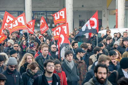 nationwide: STRASBOURG, FRANCE - 9 MAR 2016: Crowd marching with Communist flags as thousands of people demonstrate as part of nationwide day of protest against proposed labor reforms by Socialist Government