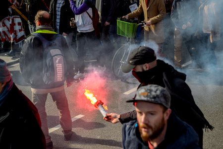 nationwide: STRASBOURG, FRANCE - 9 MAR 2016: Man with red signal fire torch in city center as thousands of people demonstrate as part of nationwide day of protest against proposed labor reforms by Socialist Government Editorial