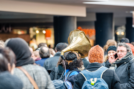 socialist: STRASBOURG, FRANCE - 9 MAR 2016: Woman wearing megaphone on head as thousands of people demonstrate as part of nationwide day of protest against proposed labor reforms by Socialist Government