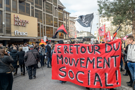 nationwide: STRASBOURG, FRANCE - 9 MAR 2016: The return of social movement banner hold by people as thousands of people demonstrate as part of nationwide day of protest against proposed labor reforms by Socialist Government