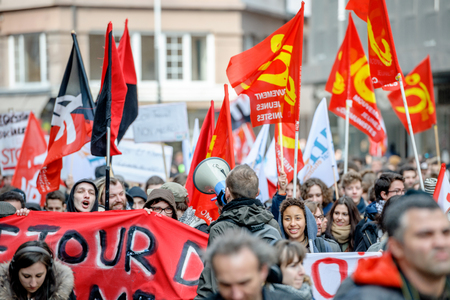 plackard: STRASBOURG, FRANCE - 9 MAR 2016: Young people holding plackard as thousands of people demonstrate as part of nationwide day of protest against proposed labor reforms by Socialist Government