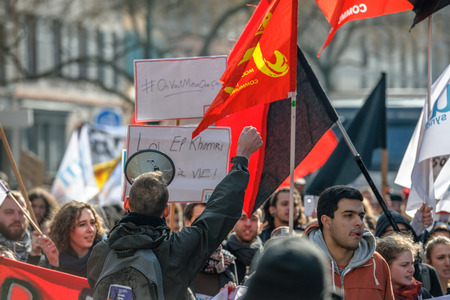 reforms: STRASBOURG, FRANCE - 9 MAR 2016: Man rising hand in front of crowd as thousands of people demonstrate as part of nationwide day of protest against proposed labor reforms by Socialist Government Editorial