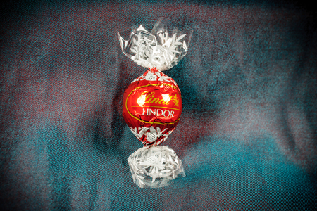 lindt: Lindt Lindor chocolate truffle on a chameleon luxury silk background. Lindt is one one of the lastgest luxury chocolate and confectionery company worldwide with more than 30 factories worldwide Editorial