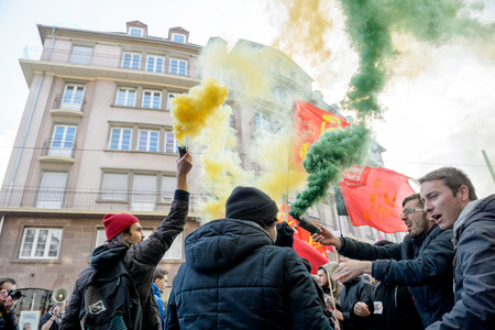 nationwide: STRASBOURG, FRANCE - 9 MAR 2016: People burn flares and smokes grenade as thousands of people demonstrate as part of nationwide day of protest against proposed labor reforms by Socialist Government