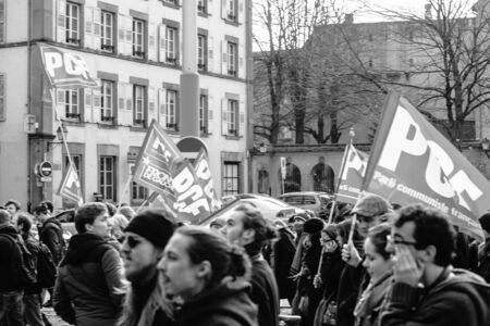 nationwide: STRASBOURG, FRANCE - 9 MAR 2016: French communist flags waving as thousands of people demonstrate as part of nationwide day of protest against proposed labor reforms by Socialist Government