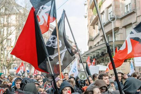drapeau pirate: STRASBOURG, FRANCE - 9 MAR 2016: Pirate flag waving above crowd as thousands of people demonstrate as part of nationwide day of protest against proposed labor reforms by Socialist Government �ditoriale