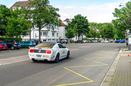 sponsorship: STRASBOURG, FRANCE - JUN 27, 2015: Ford Mustang car with racing stickers and sponsorship advertising making noise in calm neighborhood