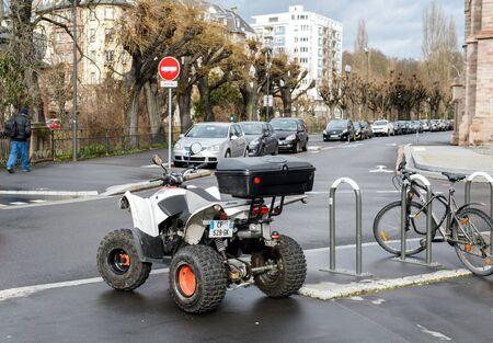 atv: STRASBOURG, FRANCE - FEB 9, 2016: AEON ATV All terrain vehicle parked near a bike in the center of the city of Strasbourg.