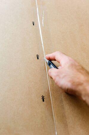 box cutter: Man cutting a cardboard box sharp steel box cutter knife to open it.