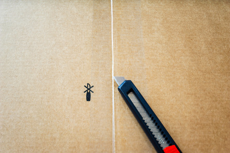 box cutter: Cutter on box of furniture just above the scotch protection tape Stock Photo