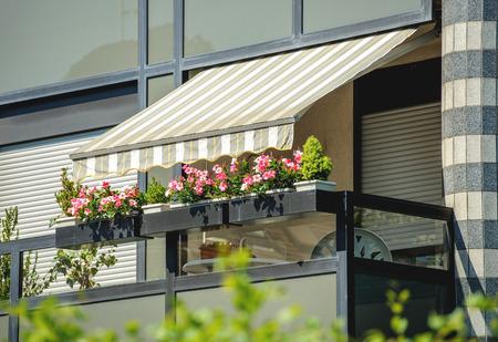 Balcón con toldo abierto y flores hermosas - cubiertos por pantalla parasol en un día caluroso de verano