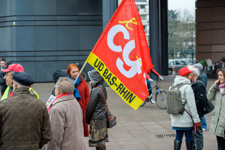 syndicate: STRASBOURG, FRANCE - MAR 15, 2016: Woman holding red Confederation Generale du Travail (C.G.T.) as hundreds protests against Bas-Rhing Alsace departmental budget cuts for 2016, requesting no cuts and wage increase Editorial