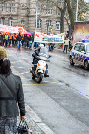 syndicate: STRASBOURG, FRANCE - MAR 15, 2016: Police scootersurveilling hundreds protests on Strasbourg streets under heavy rain against Bas-Rhin Alsace departmental budget cuts for 2016, requesting no cuts and wage increase Editorial