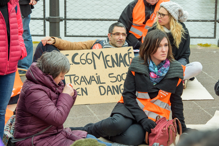 syndicate: STRASBOURG, FRANCE - MAR 15, 2016: Man holding placard as hundreds protests against Bas-Rhin Alsace departmental budget cuts for 2016, requesting no cuts and wage increase