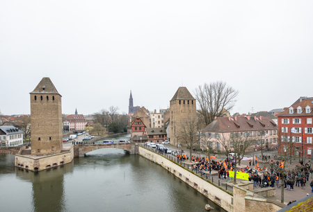 syndicate: STRASBOURG, FRANCE - MAR 15, 2016: Pont Couverts with the nearby hundreds protests against Bas-Rhing Alsace departmental budget cuts for 2016, requesting no cuts and wage increase Editorial