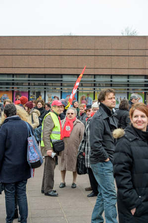 confederation: STRASBOURG, FRANCE - MAR 15, 2016: Woman holding red Confederation Generale du Travail (C.G.T.) as hundreds protests against Bas-Rhing Alsace departmental budget cuts for 2016, requesting no cuts and wage increase Editorial