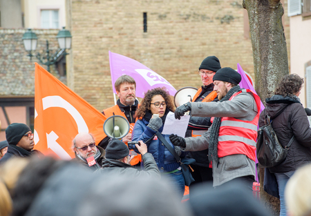 syndicate: STRASBOURG, FRANCE - MAR 15, 2016: Holding speech to crowd as hundreds protests against Bas-Rhin Alsace departmental budget cuts for 2016, requesting no cuts and wage increase