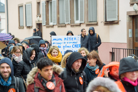 syndicate: STRASBOURG, FRANCE - MAR 15, 2016: Marching with placard as hundreds protests against Bas-Rhin Alsace departmental budget cuts for 2016, requesting no cuts and wage increase