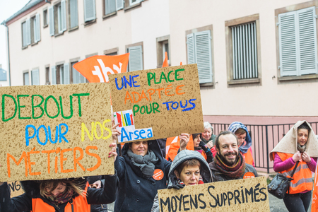 under surveillance: STRASBOURG, FRANCE - MAR 15, 2016: Start for our profession placards as hundreds protests against Bas-Rhin Alsace departmental budget cuts for 2016, requesting no cuts and wage increase