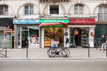 coiffure: PARIS, FRANCE - AUG 18, 2014: Paris street with Turkish Coiffure salon, Boucherie Halal, Istanbul souvenir store and pedestrian walking nearby on a summer sunny day