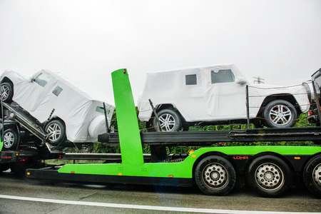 transportation company: HUNGARY - SEPTEMBER 18, 2013: New luxury Mercedes-Benz G-Class SUV cars being transported on a HODLMAYR trailer near Hungarian border. Hodlmayr is an Austrian international transportation company Editorial