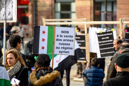 al assad: STRASBOURG, FRANCE - MAR 19, 2016: No to Russian weapons in Syria placard as Syrian diaspora protests in center of Strasbourg to denouncing the Syrian attacks and show solidarity with the Syrian people