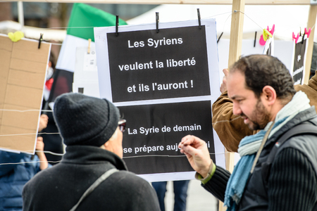 al assad: STRASBOURG, FRANCE - MAR 19, 2016: Man debating with protestor as Syrian diaspora protests in center of Strasbourg to denouncing the Syrian attacks and show solidarity with the Syrian people Editorial