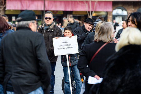 al assad: STRASBOURG, FRANCE - MAR 19, 2016: Kid holding placard No to russian occupation as Syrian diaspora protests in center of Strasbourg to denouncing the Syrian attacks and show solidarity with the Syrian people Editorial