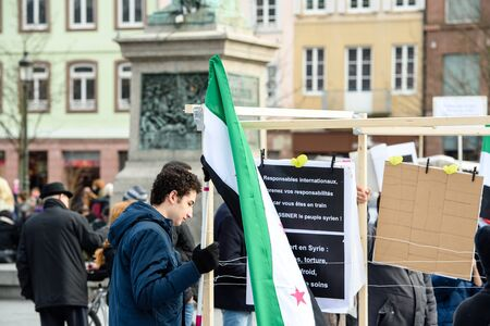 al assad: STRASBOURG, FRANCE - MAR 19, 2016: Young man holding Syrian flag as  Syrian diaspora protests in center of Strasbourg to denouncing the Syrian attacks and show solidarity with the Syrian people