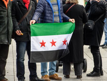 al assad: STRASBOURG, FRANCE - MAR 19, 2016: People posing Syrian flag as  Syrian diaspora protests in center of Strasbourg to denouncing the Syrian attacks and show solidarity with the Syrian people