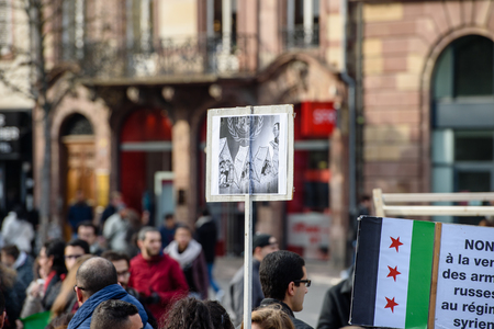 al assad: STRASBOURG, FRANCE - MAR 19, 2016: Refugee placard above people as Syrian diaspora protests in center of Strasbourg to denouncing the Syrian attacks and show solidarity with the Syrian people
