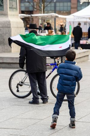 al assad: STRASBOURG, FRANCE - MAR 19, 2016: Young kid waving Syrian flag as Syrian diaspora protests in center of Strasbourg to denouncing the Syrian attacks and show solidarity with the Syrian people