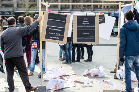 al assad: STRASBOURG, FRANCE - MAR 19, 2016: Man arranging placards as Syrian diaspora protests in center of Strasbourg to denouncing the Syrian attacks and show solidarity with the Syrian people Editorial