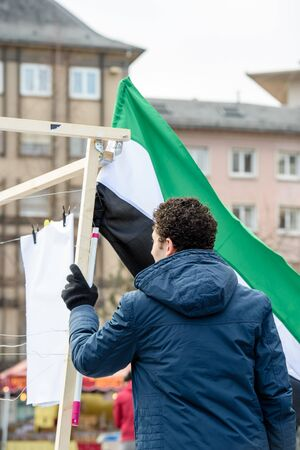 al assad: STRASBOURG, FRANCE - MAR 19, 2016: Man holding Syrian flag as Syrian diaspora protests in center of Strasbourg to denouncing the Syrian attacks and show solidarity with the Syrian people