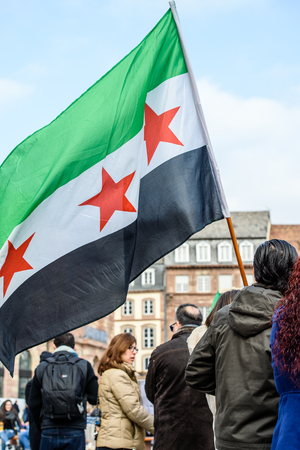 STRASBOURG, FRANCE - MAR 19, 2016: Man waving Syrian flag as Syrian diaspora protests in center of Strasbourg to denouncing the Syrian attacks and show solidarity with the Syrian people