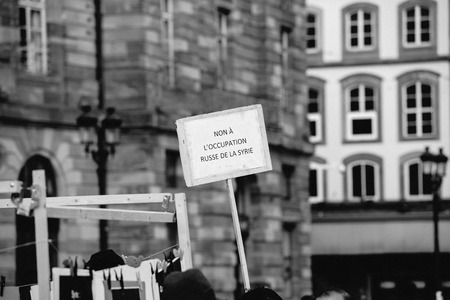 al assad: STRASBOURG, FRANCE - MAR 19, 2016: No to russian occupation placard as Syrian diaspora protests in center of Strasbourg to denouncing the Syrian attacks and show solidarity with the Syrian people
