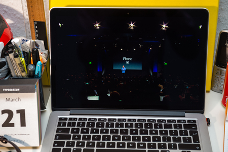 introducing: PARIS, FRANCE - MARCH 21, 2016: Apple Computers website on MacBook Pro Retina in a creative room environment showcasing Apple Event with Greg Joswiak introducing iPhone SE