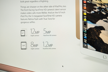 pro: PARIS, FRANCE - MARCH 21, 2016: Apple Computers website on MacBook Pro Retina in a geek creative room environment showcasing the newly announced 12 Megapixels camera on iPad Pro