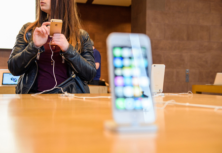 night shift: PARIS, FRANCE - APR 4, 2016: People testing new iPhone with the Apple iPhone SE in docking station during the sales launch of the latest Apple Inc. smartphone and iPad Pro at the Apple store in Paris, France