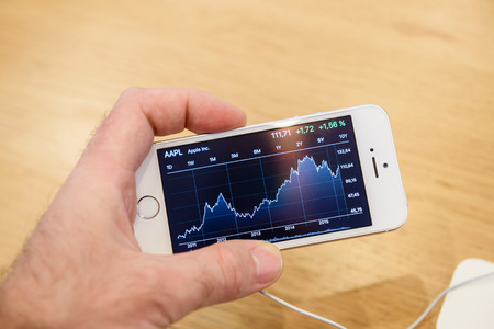 stock market launch: PARIS, FRANCE - APR 4, 2016: Man looking at the Apple stock chart on the new Apple iPhone SE during the sales launch of the latest Apple Inc. smartphone and iPad Pro at the Apple store in Paris, France