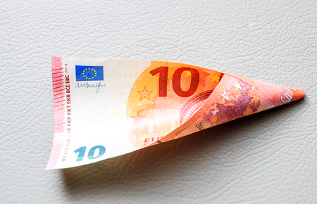 paper currency: Ten Euro paper currency wraped in tubular shape on leather background