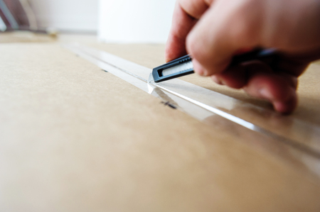box cutter: Man cutting with sharp cutter knife a cardboard box to open it before installing furniture