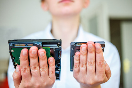ssd: IT specialist hands holding fast flash SSD - solid state drive and Hard Drive Disk HDD