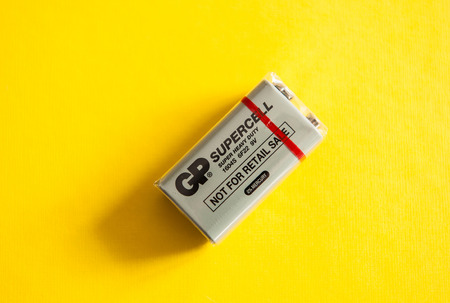gp: PARIS, FRANCE - MAR 02, 2015: New nine-volt battery or 9-volt battery on a yellow background made by GP Supercell - Super Heavy Duty with 0% mercury. The standard name for this battery is PP3-size 9-volt alkaline battery Editorial