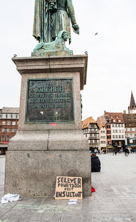 insulting: STRASBOURG, FRANCE - APR 9, 2016: French placard on General Kleber statue reading Waking up for 1200 Euro is insulting during public placard drawings in Place Kleber