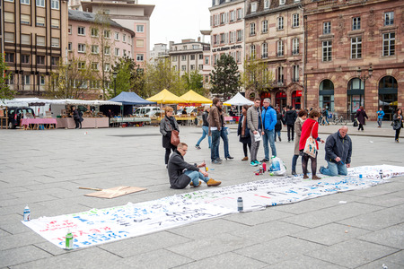 proposed: STRASBOURG, FRANCE - APR 9, 2016: People making placards during public placard drawings in Place Kleber for the upcoming protests against proposed labor reforms by Socialist Government Editorial