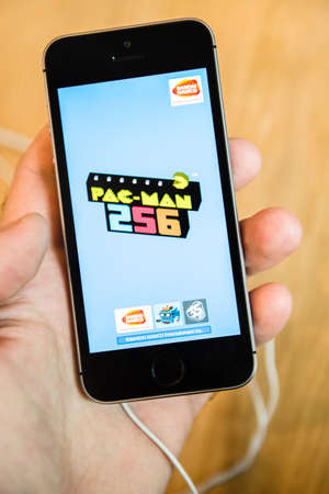 se: STRASBOURG, FRANCE - APR 9, 2016: Recently launched iPhone SE smartphone mobile phone with PAC-MAn 256 game app runing testing deciding to buy it. iPhone SE was released on March 31, 2016
