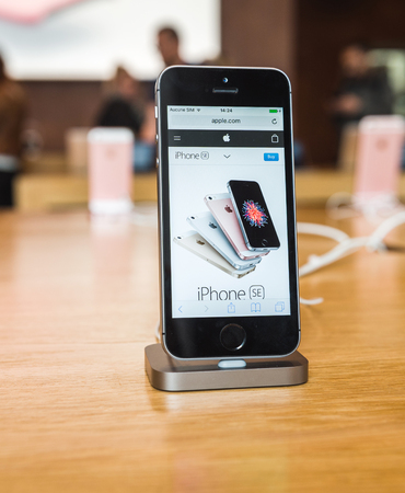 tends: STRASBOURG, FRANCE - APR 9, 2016: New iPhone SE in docking station with Apple.com page opened. New Apple iPhone tends to become one of the most popular smart phones in the world.